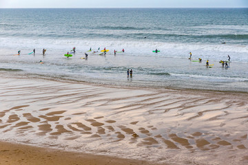 Unrecognisable surfers in the water on the Atlantic coast of France near Lacanau-Ocean, Bordeaux, France