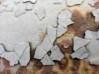 Old cracked gray paint on rusty metal