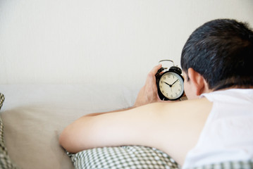 Sleepy man holding the alarm clock in the morning with late wake up - every day life at home concept