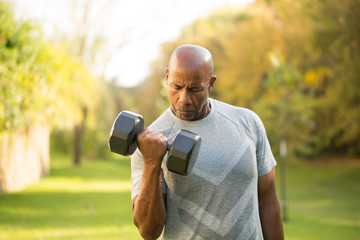 Fit African American man lifting weights outside.
