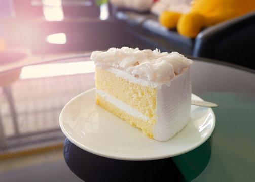Cake slice cream vanilla cake slice on white plate - Coconut cake milk dessert on table in the coffee shop