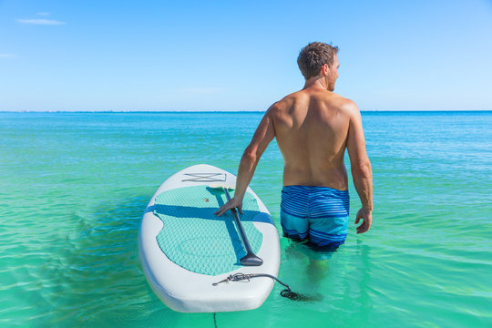 Stand up paddle boarding fitness man swimming in turquoise caribbean ocean water.