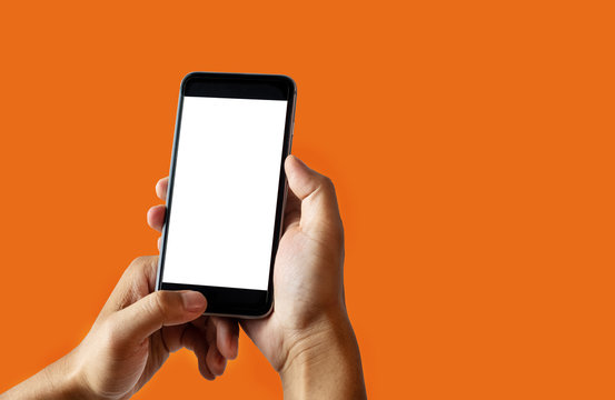 Hand holding white mobile phone with blank white screen  Orange background.