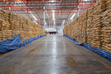 Many brown plastic white sacks with goods are in big warehouse for distribution to customer, import export logistics business.