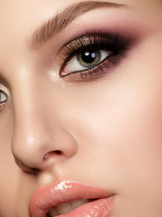 Closeup portrait of young beautiful woman with evening make up. Pink and gold multicolored smokey eyes. Luxury skincare and modern fashion makeup concept. Studio shot. Extreme closeup, partial face