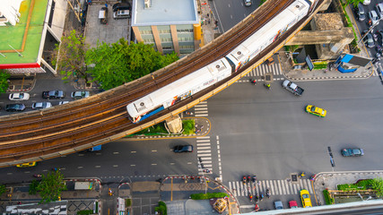 Top view aerial of a driving car on asphalt track and pedestrian crosswalk in traffic road  with sky train run on the top rail.