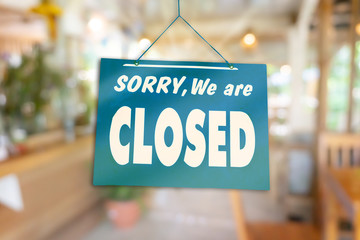 Sorry we are closed sign hang on door of business shop.