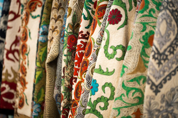 A closeup view of a colorful fabric with a traditional oriental ornament. Hand-made, traditional cloth and embroidery. Bright beautiful colors. Traditional oriental background.