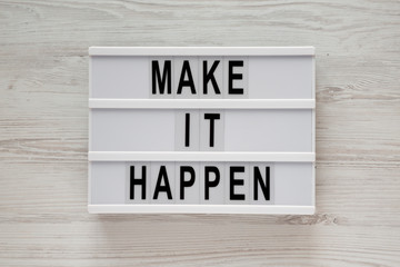 Modern board with text 'Make it happen' on a white wooden surface, top view. From above, flat lay, overhead.