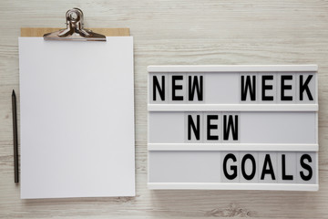 Modern board with text 'New week new goals', pencil and noticepad over white wooden background, top view. From above, flat lay, overhead.