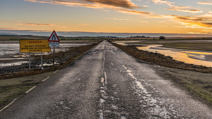 Sign: Single File Traffic, Danger do not proceed when water reaches causeway, seen on the road between Beal and Holy Island in Northumberland, England, UK Wall mural
