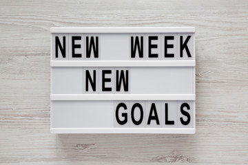 Modern board with text 'New week new goals' over white wooden surface, top view. From above, flat lay, overhead.