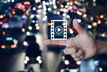 Play button with movie icon on finger over blur colorful night light city with cars in city, Business cinema online concept