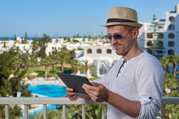 Attractive man in a white t-shirt and sunhat is using his tablet, while relaxing on the balcony of luxurious hotel.