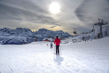 Photo sur Toile Gris ski slopes with skiers at sunset. Trentino, Italy
