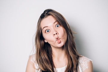 Close up indoor portrait of cool pretty young brunette girl. woman fooling around, making crazy funny grimace.