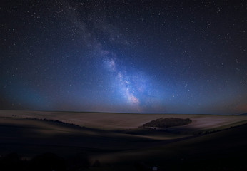 Vibrant Milky Way composite image over landscape of countryside of rolling hills and valleys