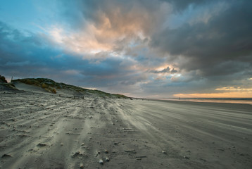 Stunning Winter sunrise over West Wittering beach in Sussex England with wind blowing sand across the beach