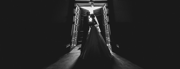 wedding couple silhouette. husband and wife are hugged at entrance or exit of the church where...