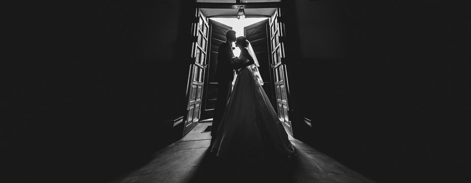 wedding couple silhouette. husband and wife are hugged at entrance or exit of the church where wedding took place,  silhouette of the love couple is visible. copy space for wedding salon advertising