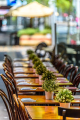 A row of chairs and tables at a outdoor cafe on Lygon Street, Carlton, Melbourne, Australia