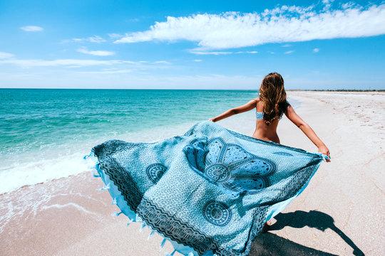 Girl holding pareo on the beach
