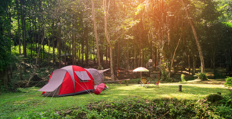 nature landscape red camping tent with tree on green grass meadow and waterfall in jungle for trekking picnic on holiday relax and vacation travel on winter or summer with warm sunlight at Pha Tat
