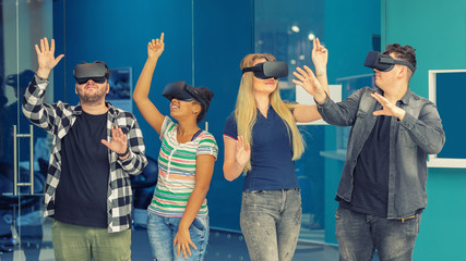 Multiracial friends group playing on vr glasses indoors. Virtual reality and wearable tech concept with young people having fun together connecting with headset goggles. Digital generation trends