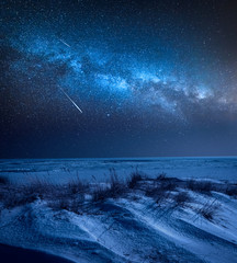 Milky way over frozen beach in winter at night