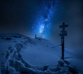 Milky way and signpost on top of mountain in winter