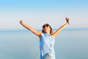 Happy young brunette woman open her arms to the sky and sea