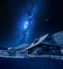 Milky way over wooden mountain cottage in winter, Poland
