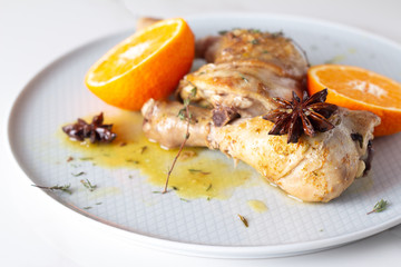 baked chicken with spices and tangerines close up.