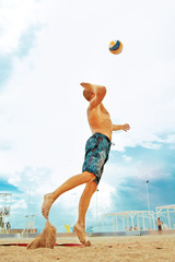 Volleyball beach player is a male athlete volleyball player getting ready to serve the ball on the beach.
