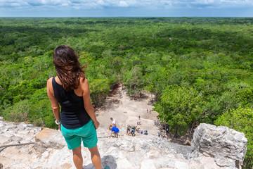 Touristin schaut von der Spitze der Nohoch Mul Pyramide in Coba, Mexiko, über den Regenwald und genießt die Aussicht
