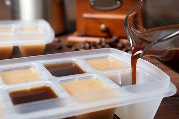 Pouring coffee in ice cube tray on table, closeup