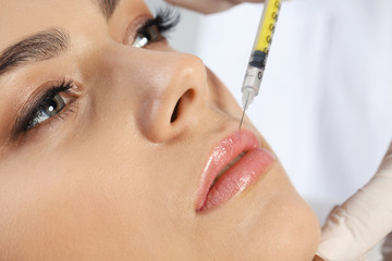 Young woman getting lips injection in clinic, closeup. Cosmetic surgery