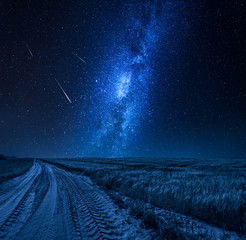 Blue milky way over field with country road at night
