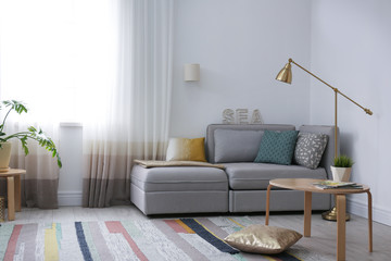 Modern living room interior with comfortable sofa near window