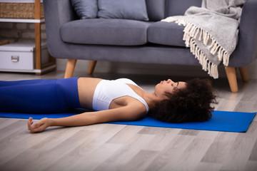 Woman Lying On Blue Yoga Mat