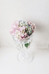 Countryside still life. Beautiful hydrangea flowers in vintage glass with water on rustic white wood of old windowsill. Happy mothers day. Creative tender spring image