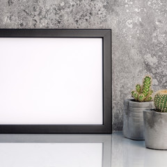 Black empty mockup frame on the background of a stone wall. Cactuses in concrete.. diy pots. White smooth shelf. Real photo. Place for text