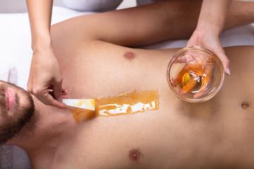 Therapist Applying Wax On Man's Chest