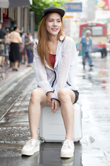 beautiful Young Asian women tourist traveler smiling in sitting on luggage on the Traffic Road in China town Yaowarat city bangkok thailand . girl waiting for a taxi car or bus , Tuk Tuk  after rainy