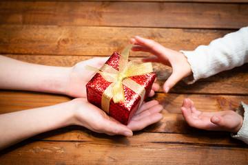 プレゼントを渡す親子の手