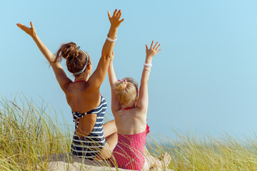 modern mother and child in swimwear on ocean shore rejoicing