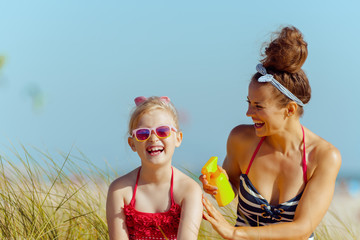 happy young mother and child on ocean coast applying SPF