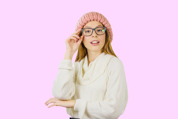 Portrait of a young red-haired girl in a knitted pink hat who is holding glasses with her hand looking at the camera on an isolated background, fashion show