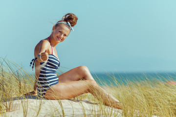 smiling modern woman playing with sand on seashore