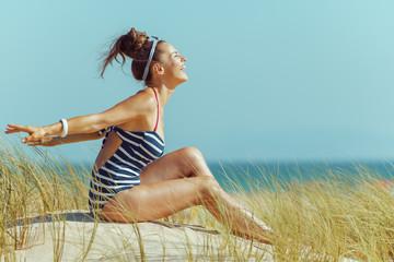 happy modern woman in striped swimwear on beach rejoicing